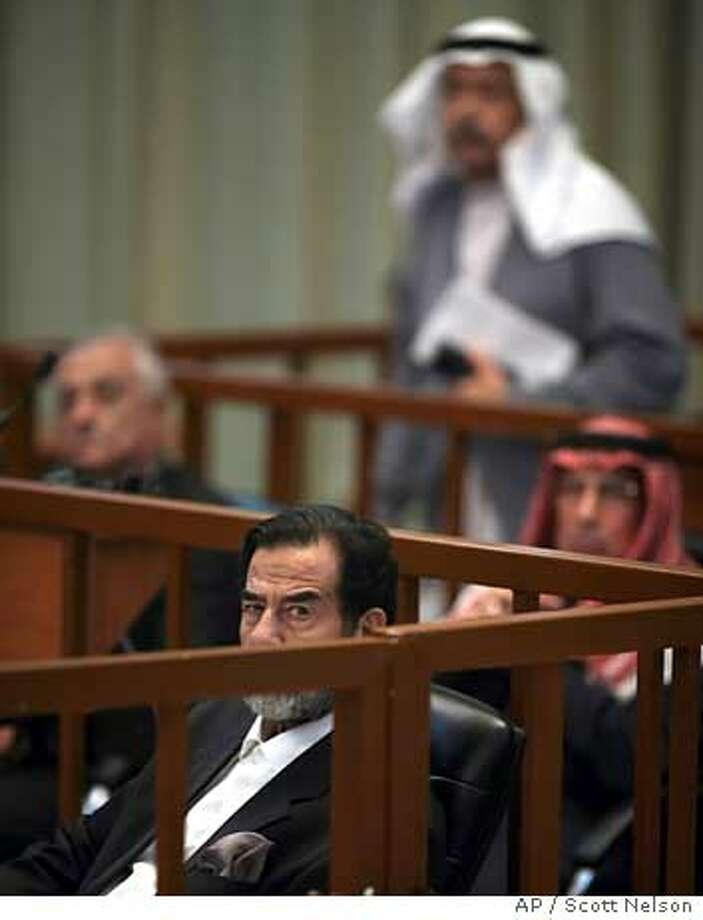 Former Iraqi leader Saddam Hussein, front center, listens to testimony during his trial inside the heavily fortified Green Zone Tuesday, Nov. 7, 2006 in Baghdad, Iraq. Hussein and 6 other defendants are facing charges of crimes against humanity for their roles in the Anfal military operation from 1987-88 that prosecutors say killed thousands of Iraqis. (AP Photo/Scott Nelson, Pool) Photo: SCOTT NELSON