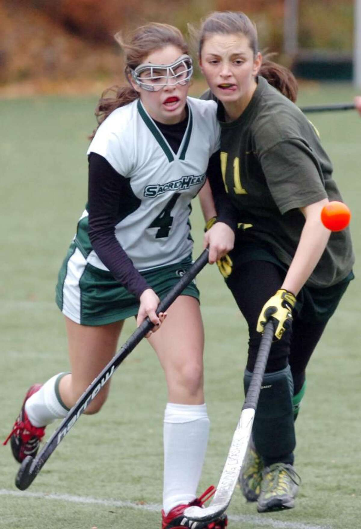 Sacred Heart's Anne Verrochi fights GA's Sarah Canning for the ball as Greenwich Academy hosts the Convent of the Sacred Heart in the FAA Field Hockey Finals. GA won 4-2.
