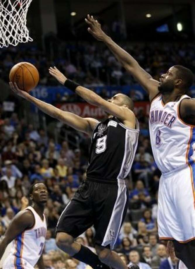 San Antonio Spurs guard Tony Parker, of France (9) shoots in between Oklahoma City Thunder guard Royal Ivey (7) and center Nazr Mohammed (8) in the first quarter of an NBA basketball game in Oklahoma City, Friday, March 16, 2012. SAn Antonio won 114-105. (AP Photo/Sue Ogrocki) (AP)