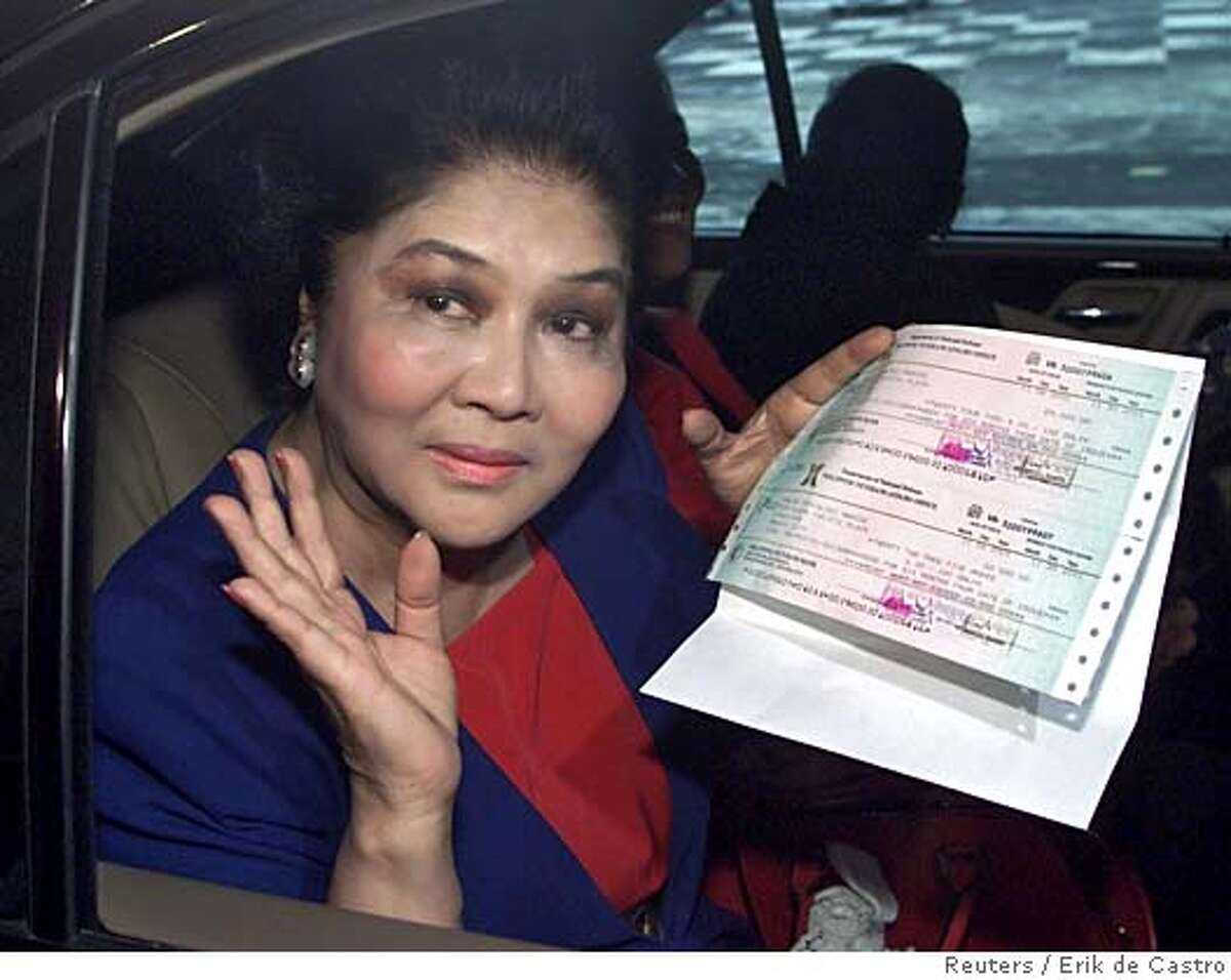 Former Philippine First lady Imelda Marcos holds two checks she received from the Department of National Defense in Manila, November 7, 2001. The Philippine government on Wednesday posthumously awarded about $900 in pension payments to dictator Ferdinand Marcos, whom it has accused of plundering hundreds of millions of dollars from the economy during his rule. REUTERS/Erik de Castro CAT