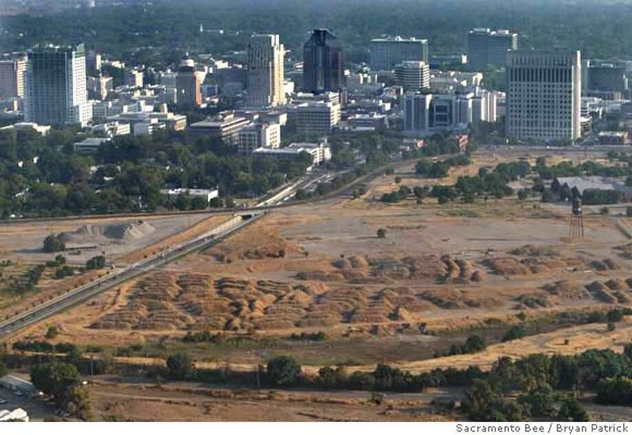 Asbestos-laden soil is mounded at the site proposed for a new Kings arena in the Union Pacific railyard downtown. The piles would have to be hauled away or buried on site and capped before the arena could be built, according to a spokeswoman for the state toxics control department. Picture taken August 2, 2006. Sacramento Bee Bryan Patrick, Aerial a1z Photo: Bryan Patrick