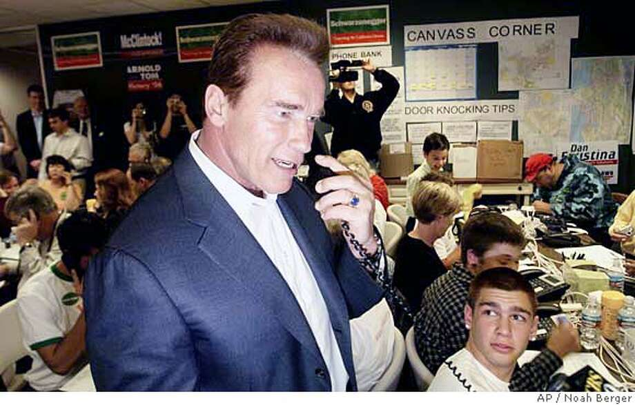 California Gov. Arnold Schwarzenegger fields a phone call with a potential voter while visiting the Republican Party's Pleasanton, Calif., volunteer center on Saturday, Nov. 4, 2006. (AP Photo/Noah Berger) Photo: NOAH BERGER
