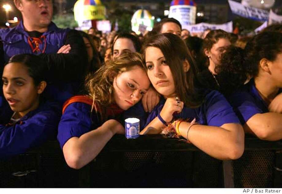 Girls attend a rally as thousands of Israelis gather in Rabin Square in Tel Aviv Saturday Nov. 4, 2006 to commemorate the 11th anniversary of Prime Minister Yitzhak Rabin's death. Rabin was killed by a Jewish extremist in 1995.(AP Photos/Baz Ratner) Photo: BAZ RATNER
