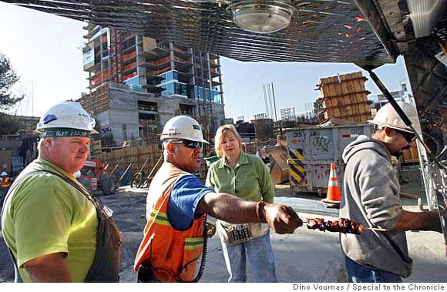 photo by Dino Vournas 10/27/06 for the SF Chronicle  Mary Nelson, third from left, chats with construction workers as her lunchwagon makes a stop at the One Rincon Hill condo tower site during the crew's morning break. Shish-kebab is one of the favored items on the menu. Dino Vournas/Special to The Chronicle Photo: Dino Vournas