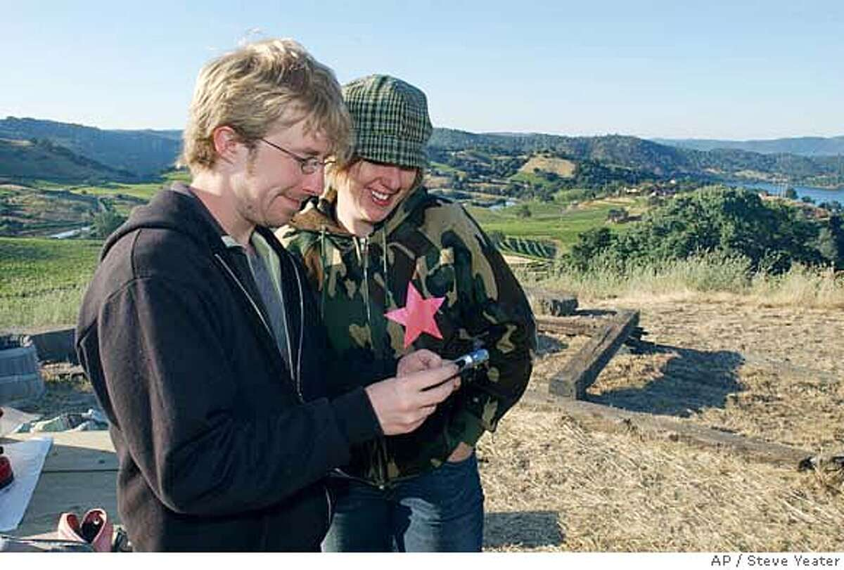 Wine camp organizers Chris Messina, left, and Tara Hunt get directions to Stevenot Winery on a Blackberry at the campsite near Murphys, Calif., on Sunday, May 28, 2006.(Photo/Steve Yeater)