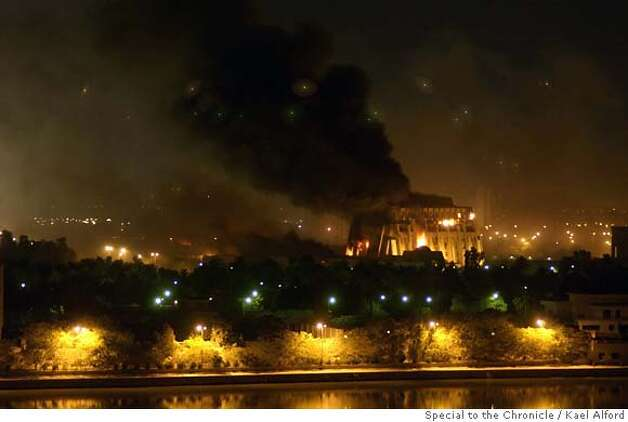 The foreign ministry palace burns while anti-aircraft flak fills the skies over the Baghdad skyline during the second night of US bombing of the Iraqi capital. Bombing began at approximately 8:30pm and continued for more than an hour hitting several large targets in the heart of the city including the foreign ministry palace. Photo: Kael Alford  21 March 2003 Photo: Kael Alford