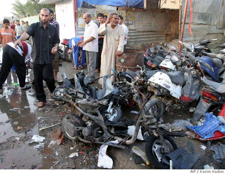 Iraqis stand by destroyed motorcycles at Mereidi market which specialized in scooters and motorbikes in Shiite enclave of Sadr City Baghdad Thursday Nov. 2, 2006, Four people were killed and 43 were wounded when an explosive laden motorcycle blew up. (AP Photo/Karim Kadim) Photo: KARIM KADIM