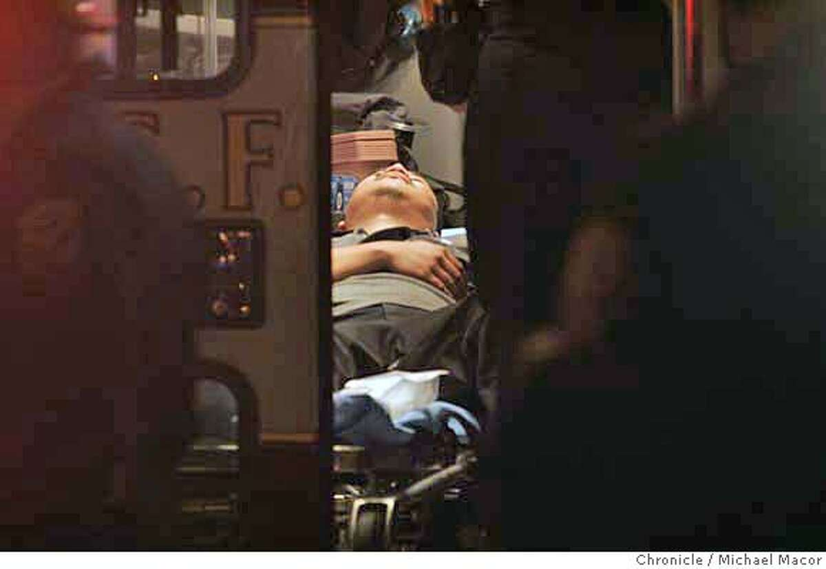 One of the injured is tended to inside an ambulance on the scene in the Castro district of San Francisco Tuesday night Oct. 31, 2006. Seven people were shot as a massive Halloween street party in the city's Castro district wound down Tuesday night, police said. The shootings occurred around 10:40 p.m., as authorities began dispersing thousands of revelers under a new curfew that was aimed at controlling the traditionally raucous event. (AP Photo/ Michael Macor - San Francisco Chronicle) MANDATORY CREDIT FOR PHOTOGRAPHER AND SAN FRANCISCO CHRONICLE / MAGAZINES OUT