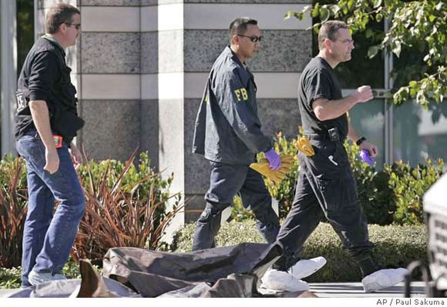 FBI and ATF agents walk past debris from a building at eBay's PayPal division Wednesday, Nov. 1, 2006 in San Jose, Calif., as they look for clues about a Halloween night explosion that shattered a window and forced the evacuation of dozens of employees. Investigators have determined that an explosive device caused the blast Tuesday on the first floor of the company's network operations center, said PayPal spokeswoman Amanda Pires. (AP Photo/Paul Sakuma) Photo: PAUL SAKUMA