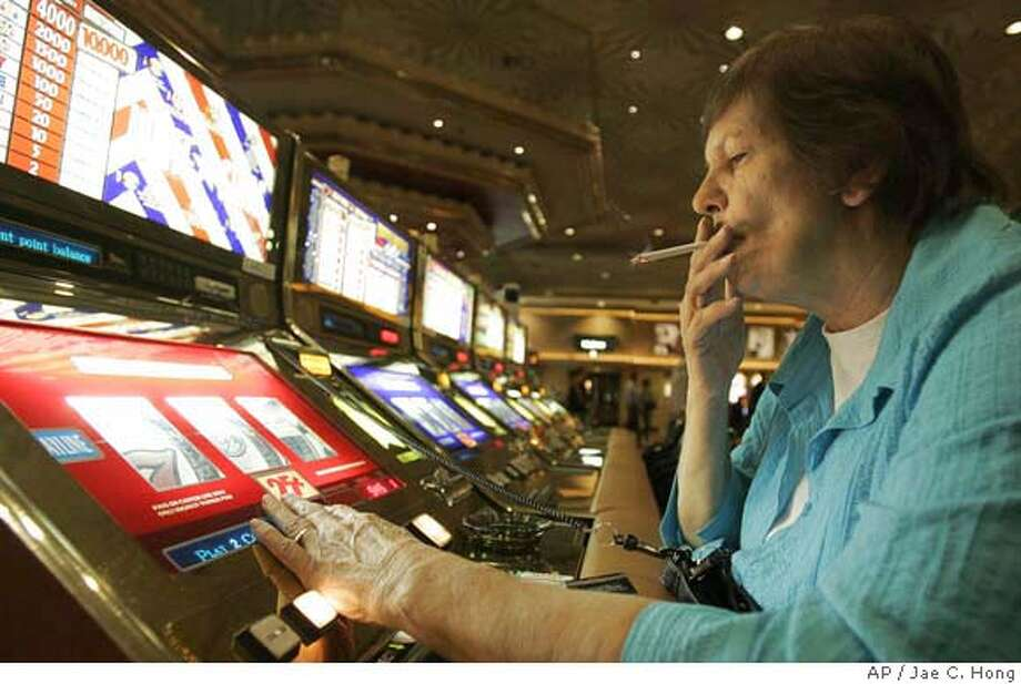 Judy King of Daytona Beach, Fla., holds her cigarette while playing a slot machine at the MGM Grand hotel-casino in Las Vegas, on Wednesday, Dec. 28, 2005. Nevada casinos, bars, convenience stores and other venues with slot machines are facing the possibility of an anti-smoking ballot initiative called the Nevada Clean Indoor Air Act, which would prevent smoking in bars and taverns that also serve food. Smoking bans hurt casino business because some gamblers prefer to smoke, said Frank Fahrenkopf Jr., association chief executive. (AP Photo/Jae C. Hong Photo: JAE C. HONG
