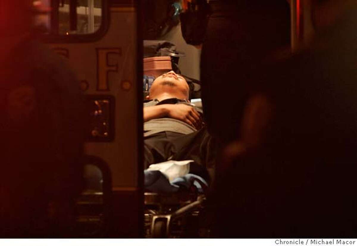 One of the injured is tended too inside an ambulance on the scene. Reports of a multiple shooting on the 2200 block of Market St., police secure the area. Halloween in the Castro of San Francisco. Event in, San Francisco, Ca, on 11/1/06. Photo by: Michael Macor/ San Francisco Chronicle