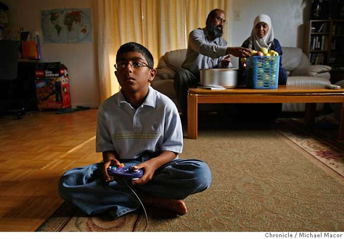 ameen15_086_mac.jpg As Ajaz Khan and his wife Sadia sort through apples picked from their backyard trees, their youngest child Usama,9 is glued to the television set playing video games inside their family room of their Santa Clara home. Many devout Muslims face an added obstacle that might seem unsurmountable: They follow a Koranic prohibition against paying or receiving interest. That means they cannot utilize a standard mortgage. That was the situation for Ajaz Khan of Santa Clara, who wanted a home for himself, his and three children but was determined to follow the Koranic prohibition. Then he discovered a small, locally owned cooperative in Santa Clara that had formed expressly to help Muslims purchase homes without playing interest. Ameen Housing Cooperative, founded in 1986, has helped 25 Muslim families buy houses through a rent-to-own plan which eschews interest, but still allows the cooperative to make a profit something that is allowed in Koranic law. Event in, Santa Clara, Ca, on 10/12/06. Photo by: Michael Macor/ San Francisco Chronicle Mandatory credit for Photographer and San Francisco Chronicle / Magazines Out