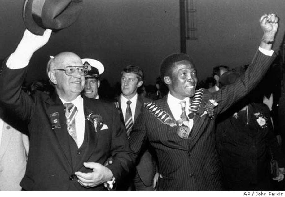 ** FILE ** President P.W. Botha waves to crowds accompanied by Lekoa Mayor Esau Mahlatsi making a black power salute in Sebokeng, South Africa on June 4, 1987 after Botha was given honorary citizenship from the mayor. It was Botha's first visit to Sebokeng and Sharpville, where anti-government riots in Sept. 1984 sparked nationwide unrest and a boycott which spread to more than 50 townships. Botha, the apartheid-era president who led South Africa through its worst racial violence and deepest international isolation, died in his sleep Tuesday, Oct. 31, 2006. He was 90. (AP Photo/John Parkin) Photo: JOHN PARKIN