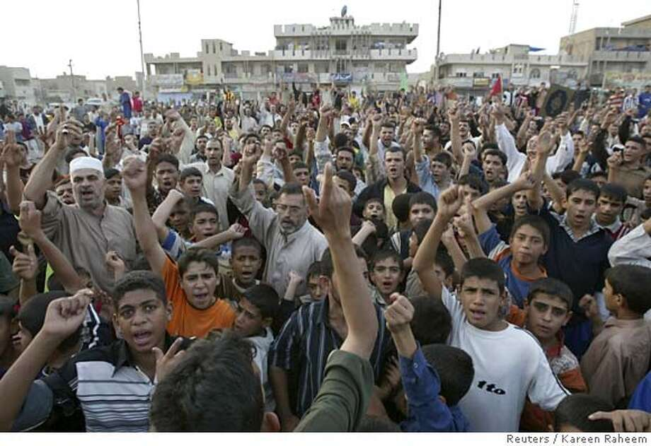 Residents chant slogans as they gather on a road after U.S. troops abandoned roadblocks in Baghdad's Sadr city, October 31, 2006. Iraq's prime minister, in a very public demonstration of his influence over the U.S. military, ordered the lifting on Tuesday of a week-old cordon around the Baghdad militia stronghold of one of his key Shi'ite allies. REUTERS/Kareen Raheem (IRAQ) 0 Photo: KAREEM RAHEEM