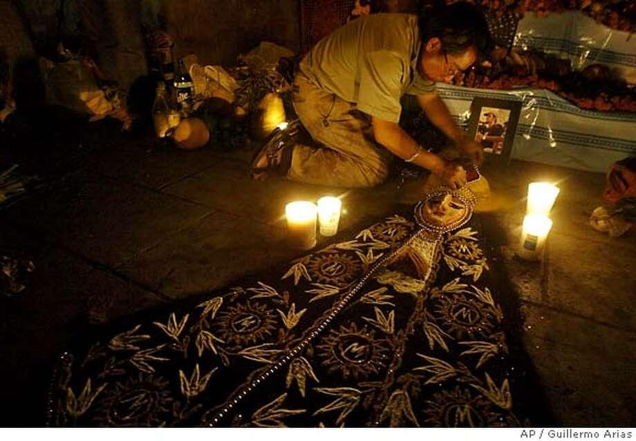 Artist Juan David Rios works on an image of La Virgen de la Soledad as a part of an altar dedicated to slain New York journalist Bradley Roland Will at the Santo Domingo plaza Tuesday, Oct. 31, 2006, in Oaxaca City, Mexico, on the Day of the Dead celebration. (AP Photo/Guillermo Arias) **EFE OUT** Photo: GUILLERMO ARIAS