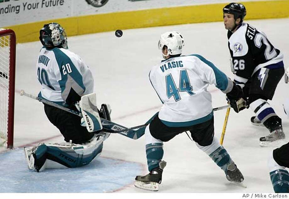 San Jose Sharks goal tender Evgeni Nabokov (20), of Kazakhstan, gives up a rebound watched by teammate Marc-Edouard Vlasic (44) and Martin St. Louis of the Tampa Bay Lightning during the first period an NHL hockey game Sunday, Oct. 29, 2006, in Tampa, Fla. (AP Photo/Mike Carlson) EFE OUT Photo: MIKE CARLSON