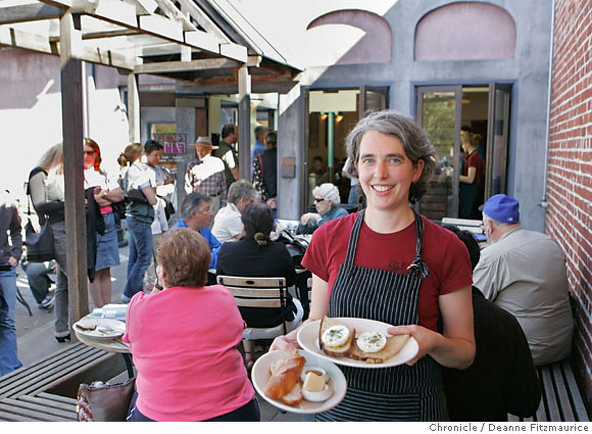Kara Dombrofski is the General Manager of Cafe Fanny's in Berkeley on 10/21/06. There is a line of people waiting to order and people sitting at outdoor tables. (Deanne Fitzmaurice/ The Chronicle) Ran on: 10-29-2006 Kara Dombrofski, the general manager of Cafe Fanny, carries a plate of poached eggs on toast and another of fresh bread. The small breakfast and lunch restaurant in Berkeley has practically made an art form out of making toast.