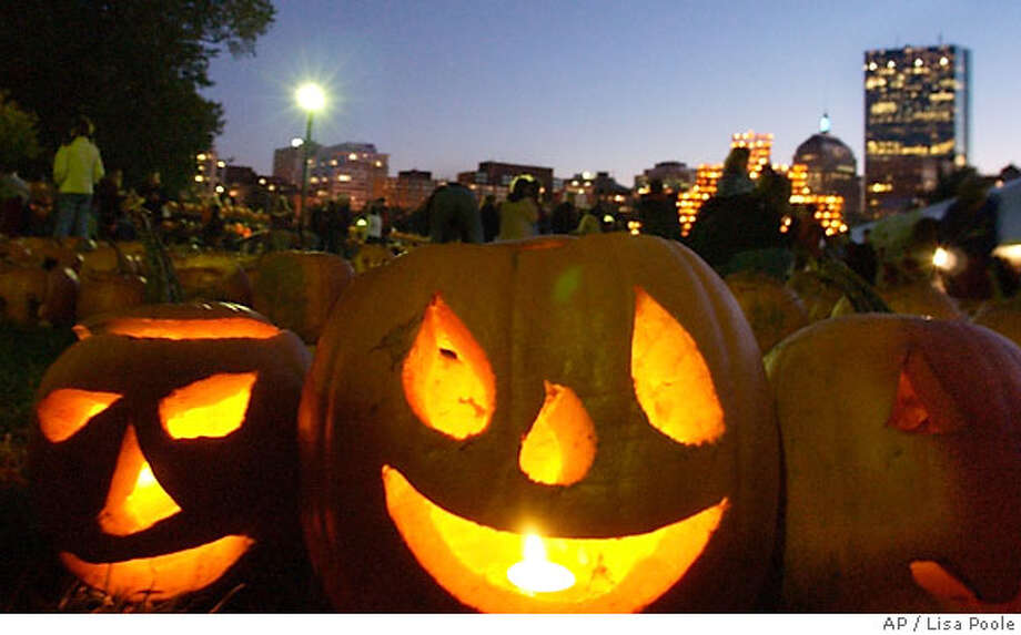 People scramble to light jack-o-lanterns during an attempt to break a world record by trying to light 30,000 pumpkins on the Boston Common, Saturday, Oct. 21, 2006, in Boston. (AP Photo/Lisa Poole) Photo: LISA POOLE