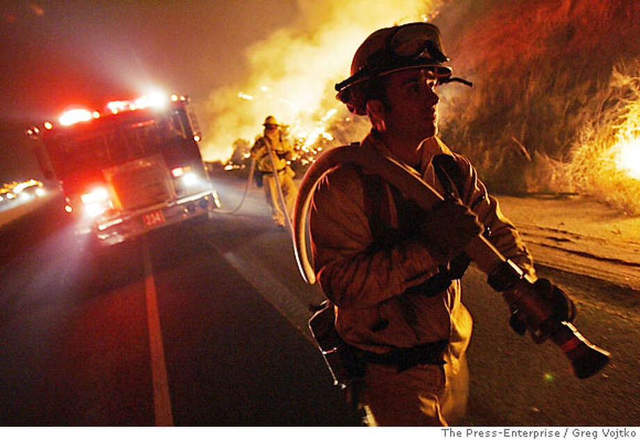 Firefighter Raymond De La Huerta keeps watch on backfires along Hwy 79/Lamb Canyon Road early Friday, Oct. 27, 2006, near Beaumont, Calif., as efforts to combat the Esperanza Fire continue. (AP Photo/The Press-Enterprise/Greg Vojtko) **MANDATORY CREDIT** , MAGS OUT. Photo: GREG VOJTKO