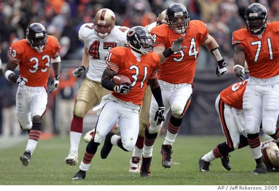 Chicago Bears' Nathan Vasher (31) runs for a 108-yard touchdown as teammates Charles Tillman (33), Brian Urlacher (54), Israel Idonije (71) and San Francisco 49ers' Billy Bajema (47) give chase with no time left in the second quarter Sunday, Nov. 13, 2005 in Chicago. Vasher returned a 52-yard missed field goal attemp that got caught up in the wind attempt for the score. (AP Photo/Jeff Roberson) Photo: JEFF ROBERSON