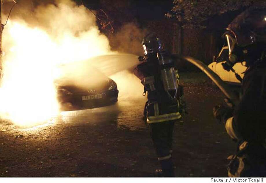 French fire-fighters extinguish the flames from a burning car in a council estate in Grigny, south of Paris, late October 26, 2006. Youth gangs around the French capital have set fire to four passenger buses in five days, a year after three weeks of civil unrest hit the Paris suburbs in 2005. REUTERS/Victor Tonelli (FRANCE) Photo: VICTOR TONELLI