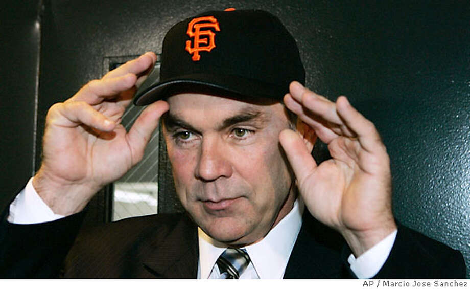 Bruce Bochy tries on a San Francisco Giants hat after being introduced as the team's' new manager in a press conference at AT&T Park in San Francisco, Friday, Oct. 27, 2006.(AP Photo/Marcio Jose Sanchez) Photo: MARCIO JOSE SANCHEZ