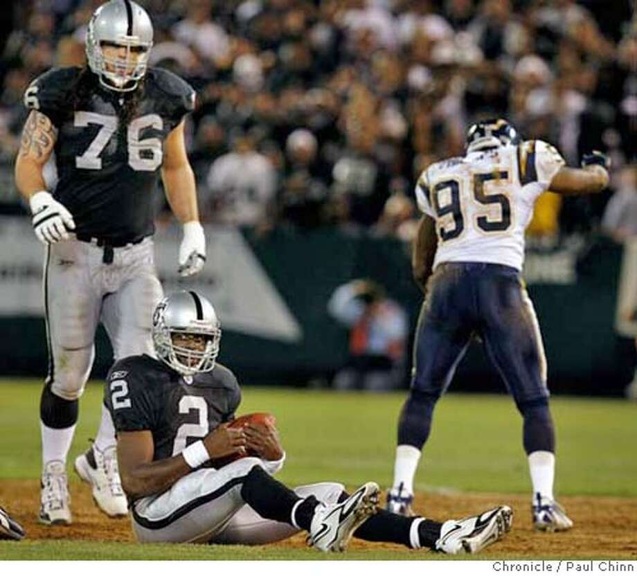 Aaron Brooks picks himself up after a Chargers sack in the first quarter of the Oakland Raiders vs. San Diego Chargers at McAfee Coliseum in Oakland, Calif. on Monday, September 11, 2006. Oakland's Robert Gallery (76) looks helpless as San Diego's Shaun Phillips (95) celebrates. PAUL CHINN/The Chronicle  **Aaron Brooks, Robert Gallery, Shaun Phillips MANDATORY CREDIT FOR PHOTOGRAPHER AND S.F. CHRONICLE/ - MAGS OUT Photo: PAUL CHINN