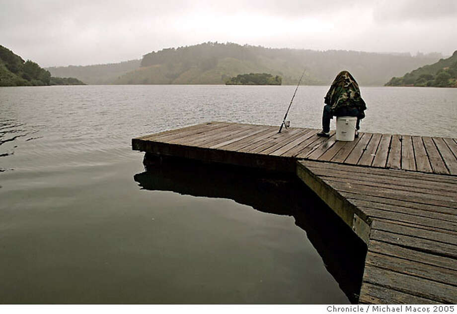 standalone_058_mac.jpg Bin Yoonsu, of Castro Valley, pulls his jacket over his head to fend off the light drizzle, as he fishes the waters of Lake Chabot Regional Park in Castro Valley. Standalone feature picture of the weather around the Bay Area as an unusual rainy day, for this time of the year, moves through the area. 6/8/05 Castro Valley, Ca Michael Macor / San Francisco Chronicle Photo: Michael Macor