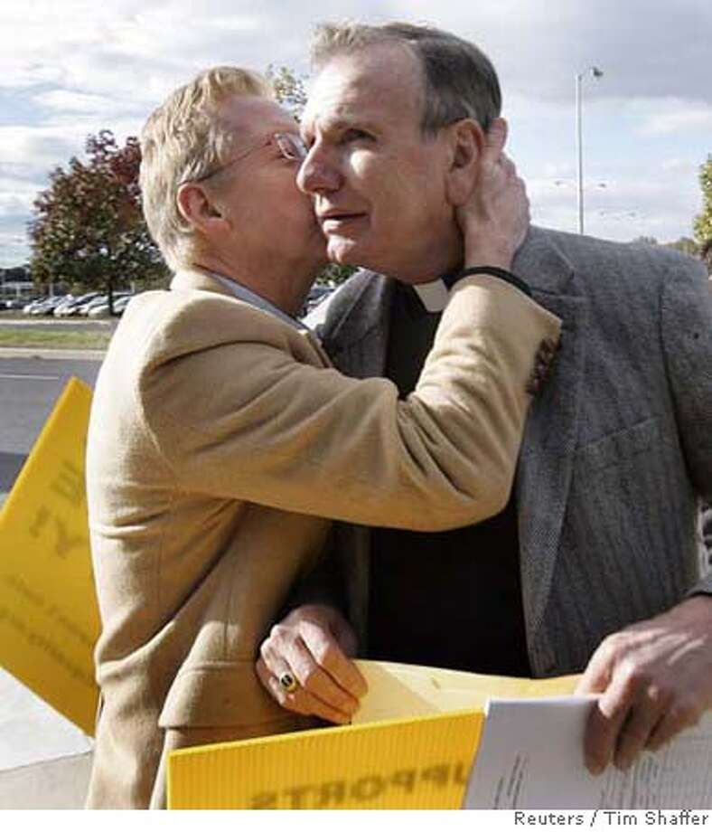 Lutheran minister Robert Kreisat (R) is embraced by his partner of 37 years Edward Mather after hearing the New Jersey Supreme court decision on same-sex marriage in front of the Supreme court building in Trenton, New Jersey, October 25, 2006. Saying that times have changed, New Jersey's highest court on Wednesday guaranteed gay couples the same rights as married heterosexual couples but left it to state lawmakers to define how the state wants to define marriage. REUTERS/ Tim Shaffer (UNITED STATES) 0 Photo: TIM SHAFFER