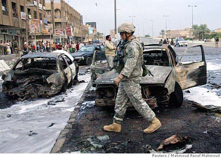 A U.S. soldier walks past burnt cars at the scene of a car bomb attack which targeted a market in Baghdad October 23, 2006. Two civilians were killed while five others were wounded in the blast, police said. REUTERS/Mahmoud Raouf Mahmoud (IRAQ) Photo: MAHMOUD RAOUF MAHMOUD