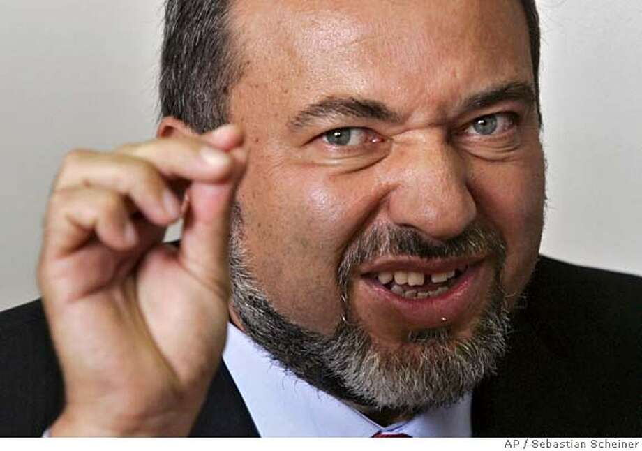 Avigdor Lieberman, leader of the right wing Yisrael Beiteinu party gestures during a party meeting at the Kenesset, Israel's Parliament, in Jerusalem, Monday Oct. 23, 2006. Israeli Prime Minister Ehud Olmert on Monday brought into his government the politician who wants to rid Israel of its Arab citizens, a move that would shore up his shaky coalition, but could hinder efforts to renew peace talks with the Palestinians. (AP Photo/Sebastian Scheiner) Photo: SEBASTIAN SCHEINER