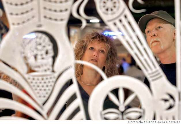 "Chris Love and her husband, Devon Ryan, of Monterey, Ca., look over an art installation at the Oakland Museum of California on Sunday, October 22, 2006. The Oakland Museum of California celebrates Days of the Dead, the Mexican tradition of honoring dead loved ones and ancestors with ""Laughing Bones/Weeping Hearts: Dia De Los Muertos 2006"". The event will be the highlight of the exhibition, and Sunday's festivities included craft activities, food, music dance performance and more.  Photo by Carlos Avila Gonzalez/The San Francisco Chronicle  Photo taken on 10/22/06, in Oakland, Ca, USA  **All names cq (source) Photo: Carlos Avila Gonzalez"