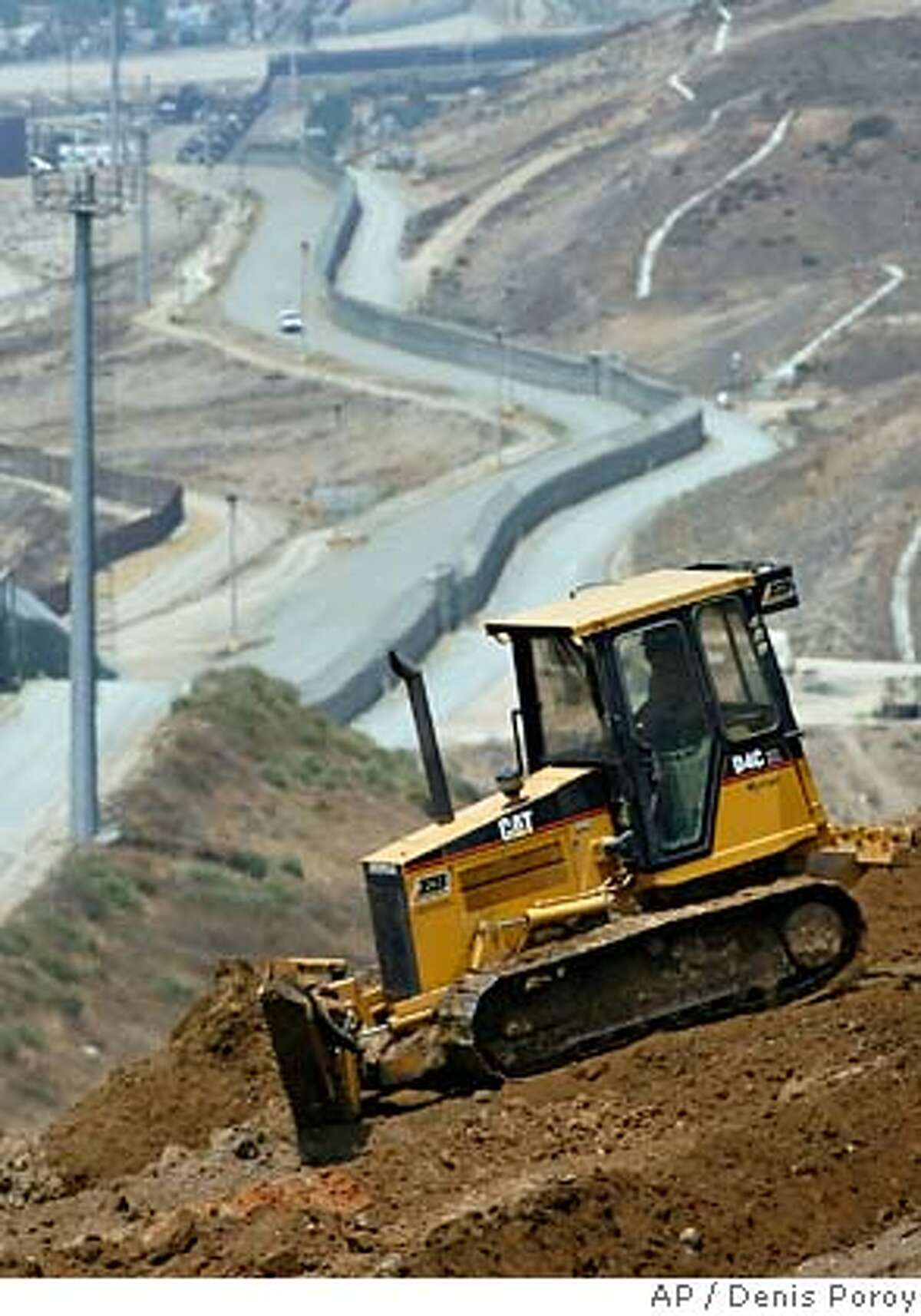 A California Army National Guardsman grades dirt with a tractor above the dual U.S.-Mexico border fences in San Diego, Wednesday, July 19, 2006. More than 900 California Army and Air National Guard personnel have reported for duty at Naval Base San Diego and are undergoing processing and training or have already taken up duties to augment federal agents along the U.S.-Mexico border in California. (AP Photo/Denis Poroy)