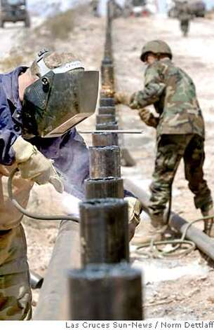 Spc. Michael Kruize, 41, front, of Cheyenne, Wyo., welds as Staff Sgt. Billy Morgan, 48, of Moorcroft, Wyo., cuts as they build an anti-vehicle barrier Monday, June 12, 2006, along the U.S.-Mexico about four miles southwest of Columbus, N.M., and four miles west of Palomas, Mexico. The two Wyoming National Guard troops with the 133rd Engineer Company are helping building the 12-mile long fence to deter vehicles from crossing the border. (AP Photo/Las Cruces Sun-News, Norm Dettlaff) Photo: NORM DETTLAFF