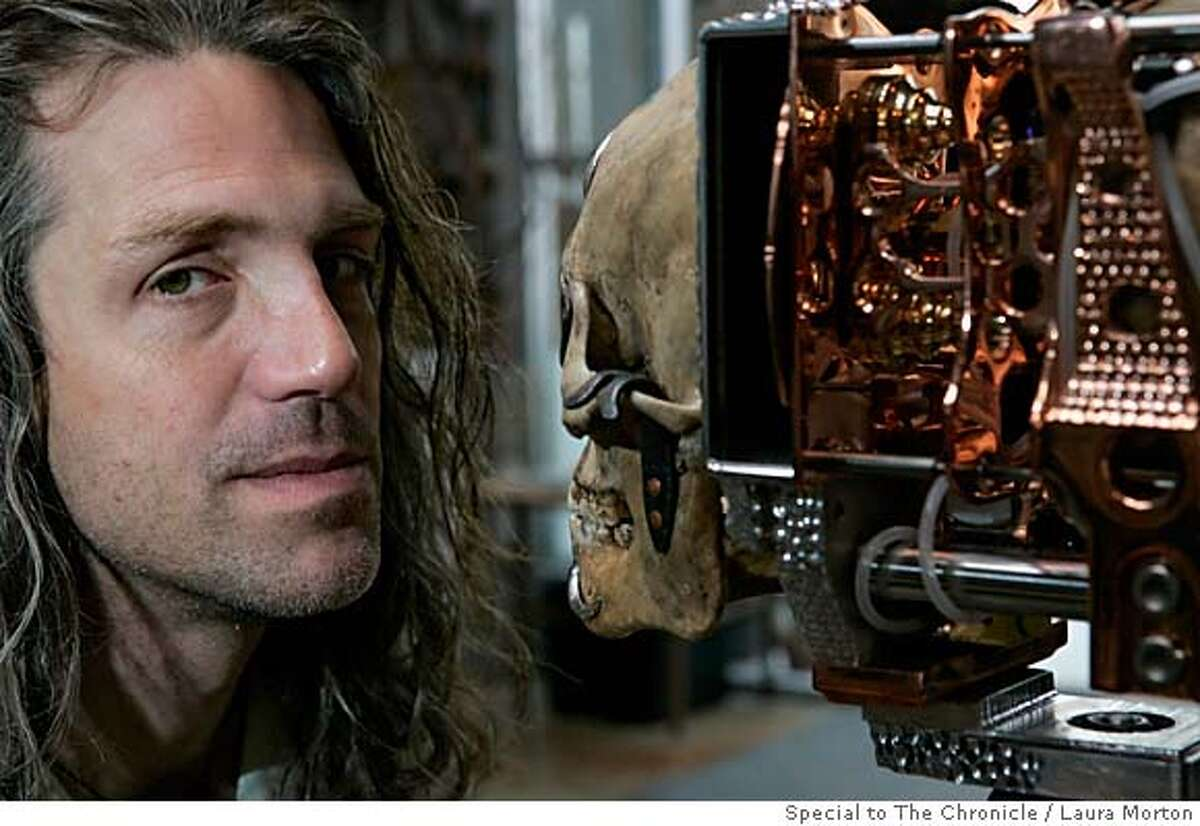 Wayne Belger poses with Yama Camera, which is made from a human skull and is one of the many pinhole camera creations on display in his exhibit