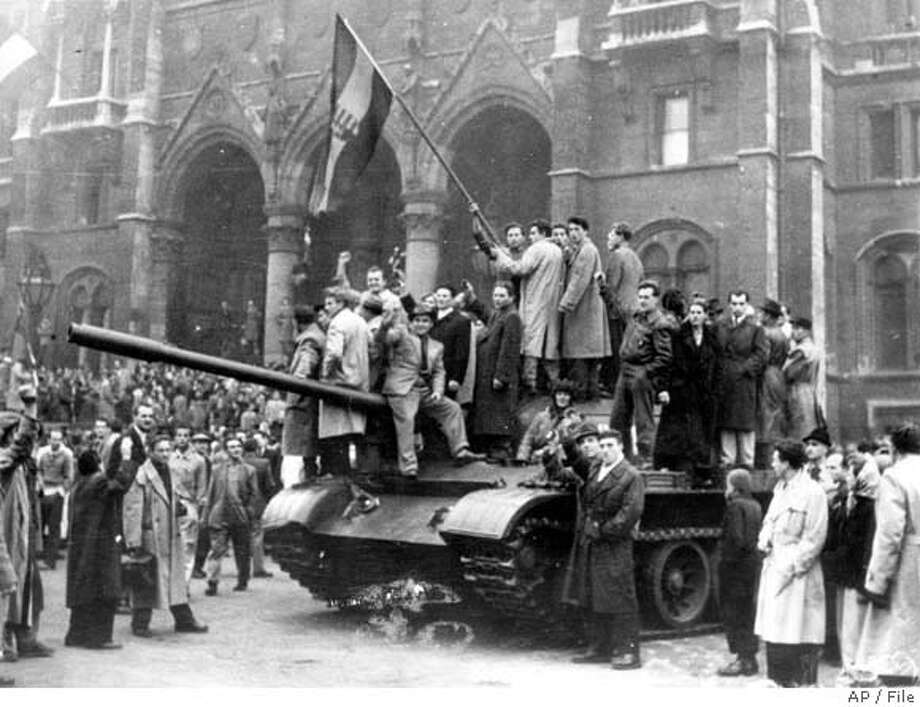 ** FILE ** Hungarian rebels wave their red, white and green national flag from a tank captured in the main square of Budapest, Hungary, in this 1956 file photo. The uprising began on Oct. 23, 1956 with demonstrations against the Stalinist regime in Budapest and was crushed eleven days later by Soviet tanks amid bitter fighting. Some 2,500 people were killed and a further 200,000 forced into exile. (AP Photo/File) Photo: Ap/file
