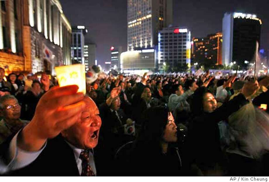 South Korean protesters denounce North Korea's nuclear test during a candlelight vigil in front of Seoul City Hall Saturday, Oct. 21, 2006. The top U.S. diplomat on Saturday rejected media reports that North Korea promised to hold off on future nuclear tests, while a former South Korean President Kim Dae-jung warned the North could lash out with military action in response to U.N. sanctions banning its weapons trade. (AP Photo/Kin Cheung) Photo: KIN CHEUNG
