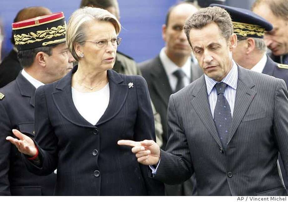 French Interior Minister Nicolas Sarkozy, right, and Defense Minister Michele Alliot-Marie Wednesday Oct. 11, 2006, in Les Essart, western France, attend a funeral ceremony for two gendarmes killed on duty last week. Conservative presidential hopeful Sarkozy has a commanding lead but Alliot-Marie, belonging to the same party, suggested again Wednesday Oct.11, 2006 that she may run for the French presidency. (AP Photo/Vincent Michel) Photo: VINCENT MICHEL