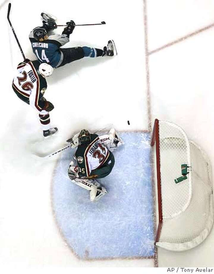 Minnesota Wild goalie Manny Fernandez blocks a shot from San Jose Sharks' Jonathan Cheechoo, top, as Kurtis Foster looks on during the first period of an NHL hockey game in San Jose, Calif., on Saturday, Oct. 21, 2006. (AP Photo/Tony Avelar) Photo: TONY AVELAR