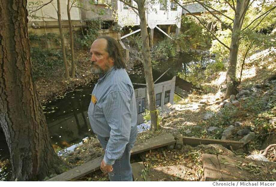 flood_067_mac.jpg McEachern believes that trees and brush need to be cleared from the creek bed to make it safe from flooding in the next coming of this year's rainy season. The back of his watch repair store is the white building behind him. Merchants in San Anselmo are up in arms, accusing the town leaders of sitting on their behinds in the wake of the New Year's Eve flood that devastated businesses downtown. Drew McEachern, the owner of Antique Time Pieces and treasurer of the San Anselmo Merchant's Association, said the town has not cleared brush, trees or debris out of the creek or helped merchants in any way, but nevertheless voted themselves raises. Every shop owner paid thousands out of their own pockets to get back in business and they are afraid this neglect will cost them money again come winter. Event in, San Anselmo, Ca, on 10/13/06. Photo by: Michael Macor/ San Francisco Chronicle Mandatory credit for Photographer and San Francisco Chronicle / Magazines Out Photo: Michael Macor