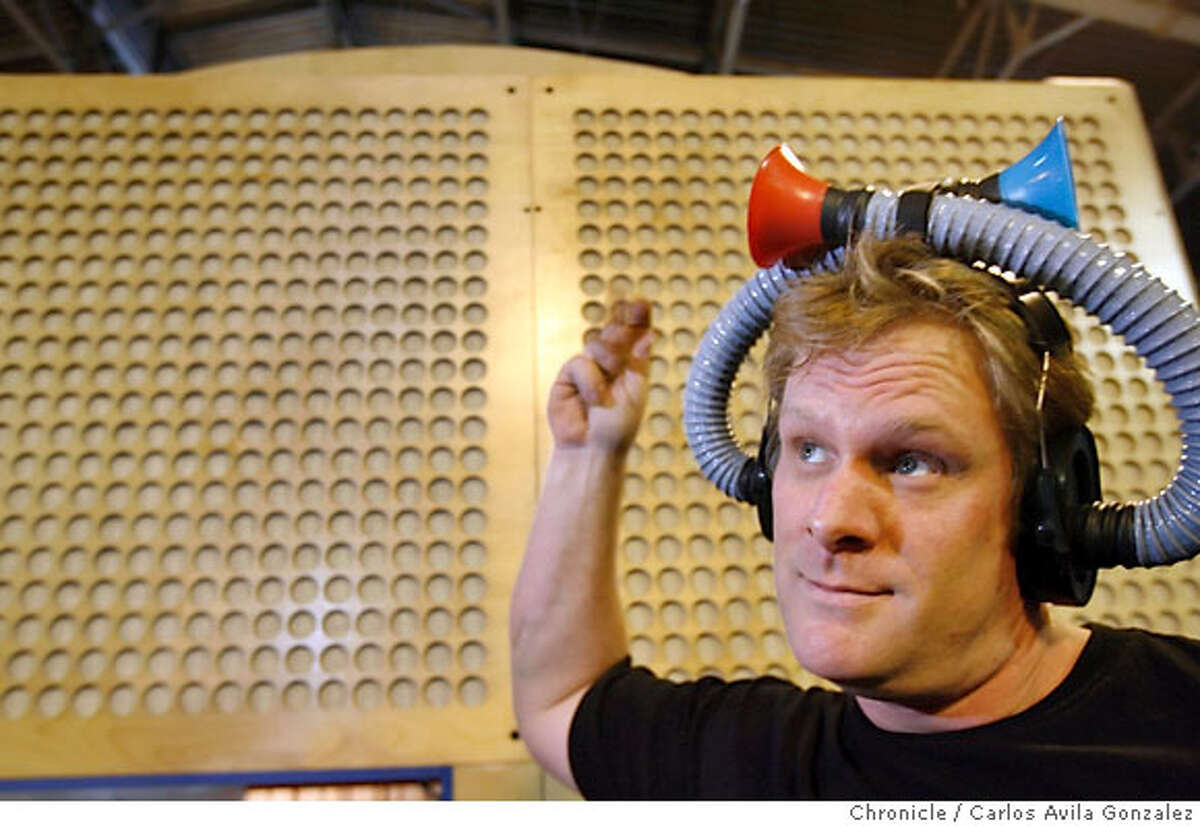 """LISTEN22_089_CAG.JPG Eric Bodine, an exhibit support technician at Exploratorium, demonstrates a device designed to disorient the listener to the direction of sound. Opening Oct. 21 The Making Sense of Sound uses natural, musical and manipulative noises to demonstrate how we hear. """"A lot of people can hear, but that doesn't mean they know how to listen,"""" says one of hte exhibits designers. """"These exhibits will show how much we often take listening and hearing for granted."""" There is a reverse headphone contraption that when you close yours eyes makes you wonder what directions sound is coming from. Photo by Carlos Avila Gonzalez/The San Francisco Chronicle Photo taken on 10/16/06, in San Francisco, Ca, USA **All names cq (source) Ran on: 10-22-2006 Eric Bodine, an exhibition support technician, tests a set of reverse headphones, which bring a new meaning to having sounds come in one ear and out the other."""