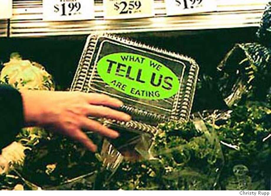 "An observer examines a mixed-media installation by Christy Rupp. ""Tell Us What We Are Eating"" is one of the artist�s proposed labels in her work, ""New Labels for Genetically Engineered Foods."" Photo by Christy Rupp"