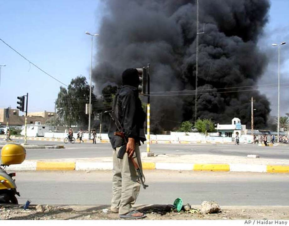 A masked gunman stands on a street corner as a building burns nearby in southern Iraqi town of Amarah, 320 kilometers (200 miles) southeast of Baghdad, Friday Oct. 20, 2006. Mahdi Army, the Shiite militia run by anti-American cleric Muqtada al-Sadr seized control of the southern Iraqi city of Amarah on Friday after their fighters stormed three main police stations Friday morning, planting explosives that flattened the buildings. (AP Photo/Haidar Hany) Photo: HAIDAR HANY