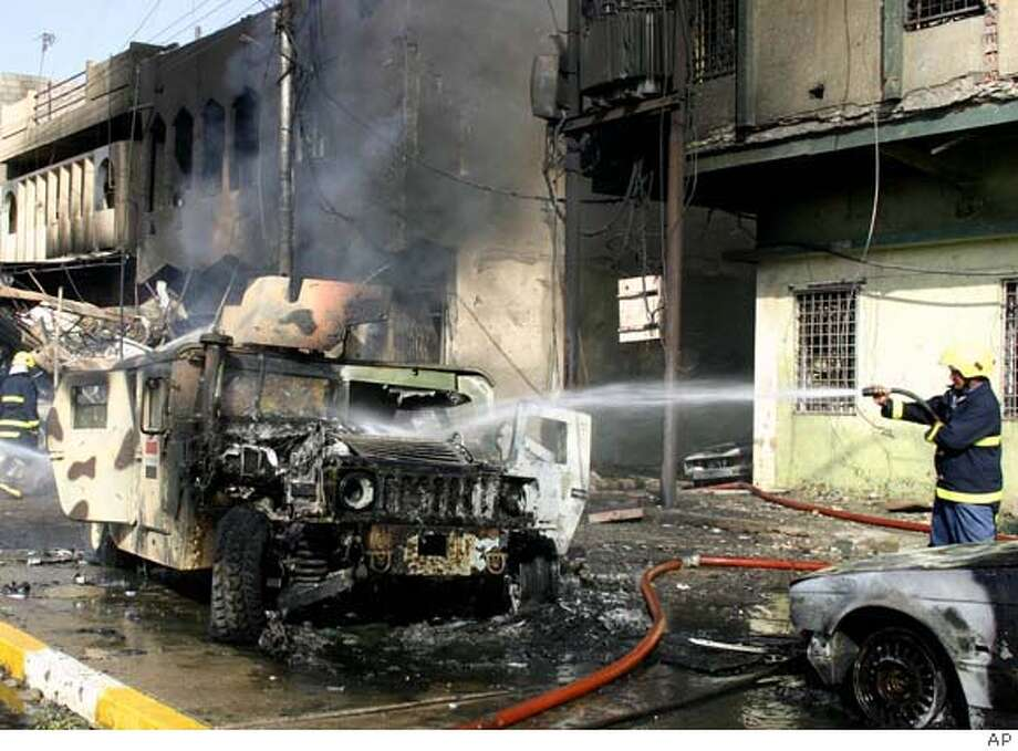 A firefighter sprays an Iraqi army humvee after a car bomb exploded in Kirkuk, Iraq, 290 kilometers (180 miles) north of Baghdad, Thursday, Oct, 19, 2006. The Kirkuk bombing was aimed at a bank where a crowd of civilians and army soldiers waited to get their wages. Twelve people, including four troops, were killed and a total of 47 were wounded, police said. (AP Photo) Photo: Ap