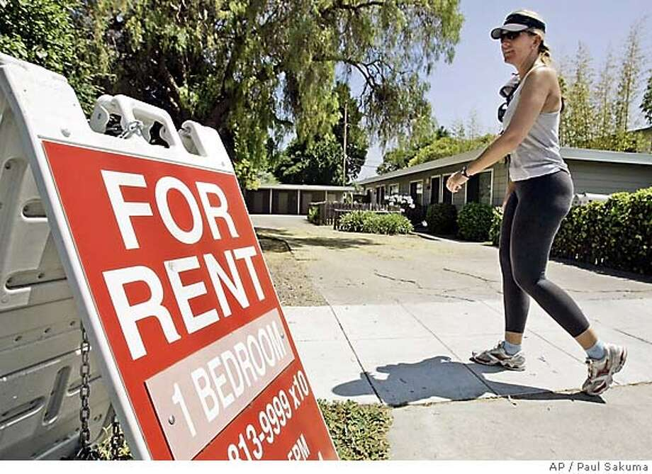 """A woman walks next to a """"For Rent"""" sign at an apartment complex in Palo Alto. Photo: PAUL SAKUMA"""