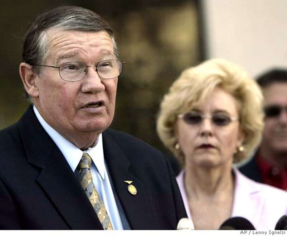 """** RETRANSMISSION FOR IMPROVED TONING ** Rep. Randy """"Duke"""" Cunningham, flanked by his wife Nancy, announces he will not seek re-election, during a news conference Thursday, July 14, 2005, in San Marcos, Calif. The eight-term San Diego-area Republican, under federal investigation for his dealings with a defense contractor, read a brief written statement and did not take questions before ducking back into a library on the California State University, San Marcos campus. (AP Photo/Lenny Ignelzi) Ran on: 07-15-2005  Randy &quo;Duke&quo; Cunningham Ran on: 07-15-2005 Ran on: 09-17-2005  Randy &quo;Duke&quo; Cunningham, an eight-term congressman from the San Diego area, is being probed on charges related to his post on a House sub- committee.  Ran on: 07-09-2006  Randy &quo;Duke&quo; Cunningham pleaded guilty to bribery.  Ran on: 07-18-2006  Pelosi RETRANSMISSION FOR IMPROVED TONING Photo: LENNY IGNELZI"""