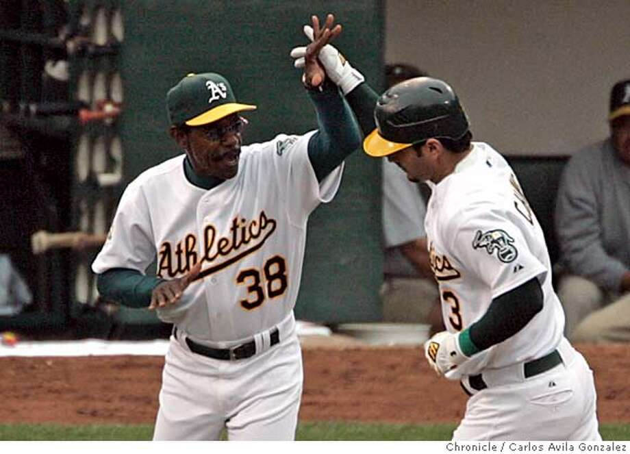 athletics_alds_cag02 Athletics third base coach Ron Washington congratulates Eric Chavez after Chavez hit a one-run homerun in the bottom of the second inning. The Oakland Athletics play the Minnesota Twins in game three of the American League Divisional Series. Event on Friday, October 6, 2006 at McAfee Stadium in Oakland, California. Carlos Avila Gonzalez / The Chronicle MANDATORY CREDIT FOR PHOTOG AND SF CHRONICLE/ -MAGS OUT Photo: Carlos Avila Gonzalez
