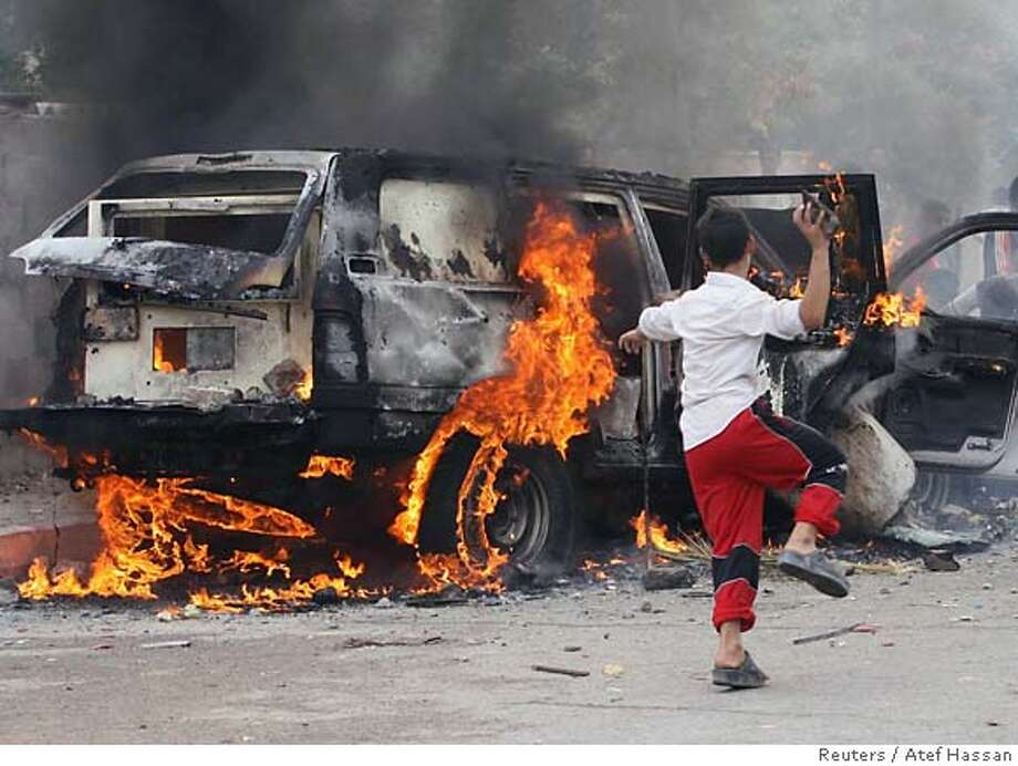 A boy throws a rock at a burning British consulate vehicle after it was attacked by gunmen with a rocket propelled grenade (RPG) launcher in Basra, 550 km (340 miles) south of Baghdad, October 16, 2006. Gunmen attacked a British consulate convoy with a RPG, wounded a foreign security guard and set fire to one of its vehicles in Basra, a British consulate spokeswoman in Basra said. REUTERS/Atef Hassan (IRAQ) Photo: ATEF HASSAN