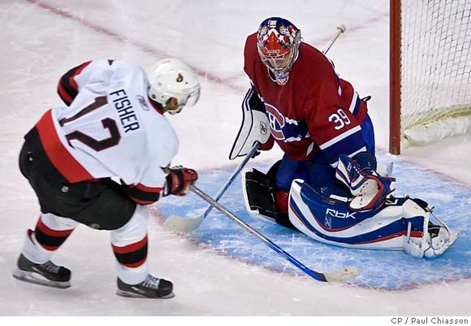 Ottawa Senators' Mike Fisher , left,scores past Montreal Canadiens goaltender Cristobal Huet during a shootout in NHL action Saturday, Oct. 14, 2006 in Montreal, Canada. The Senators beat the Canadiens, 3-2. (CP PHOTO/Paul Chiasson) Photo: PAUL CHIASSON