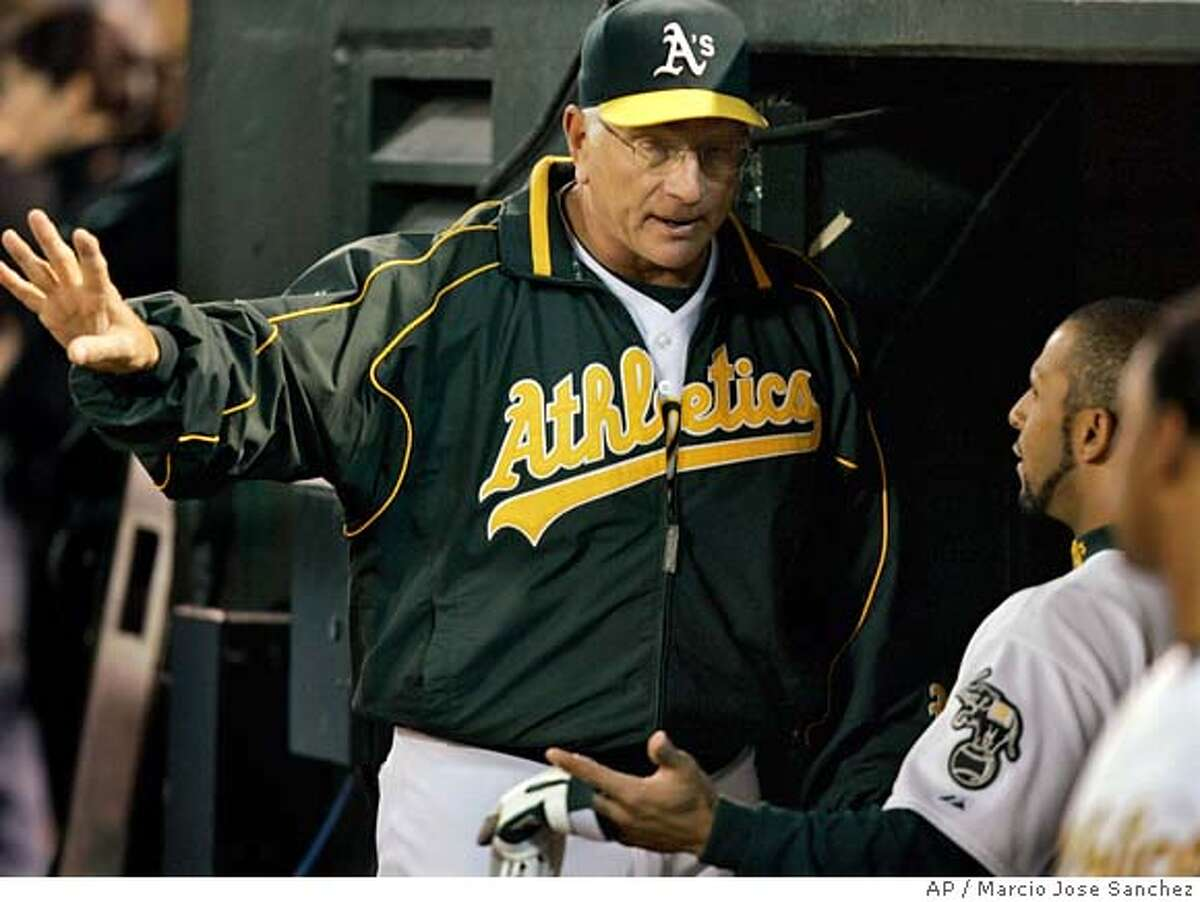 Oakland Athletics' manager Ken Macha speaks with Jay Payton after Payton hit an RBI ground out in the eighth inning against the Detroit Tigers in Game 1 of the American League Championship Series in Oakland, Calif., Tuesday, Oct. 10, 2006. The Tigers defeated the Athletics 5-1. (AP Photo/Marcio Jose Sanchez)
